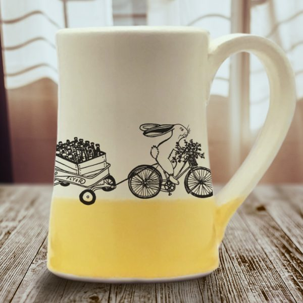 Large coffee mug handmade by hedgehogs with an illustration of yet another Ale on Wheels delivery person. This rabbit is new and not particularly fast. Gold accent color