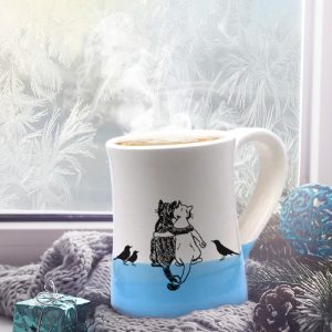 Handmade coffee mug with a drawing of a black cat, a white cat and a few blackbirds quietly enjoying each other's company. Blue accent color