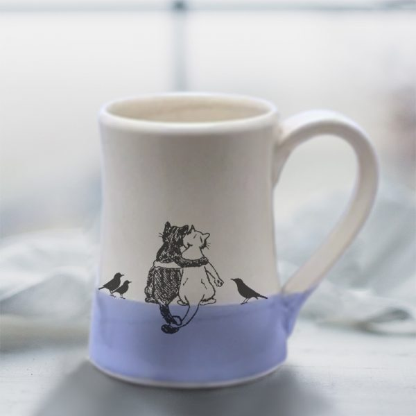 Handmade coffee mug with a drawing of a black cat, a white cat and a few blackbirds quietly enjoying each other's company. Lavender accent color