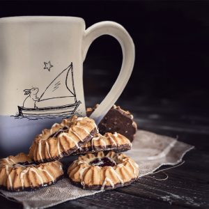 Handmade coffee mug with original illustration of a bunny sailing the high seas. Lavender accent color. Made by hedgehogs in the Blue Ridge Mountains.