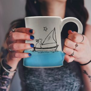 Handmade coffee mug with original illustration of a bunny sailing the high seas. Light blue accent color. Made by hedgehogs in the Blue Ridge Mountains.