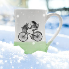 Handmade coffee mug with drawing of hedgehog delivering a Christmas tree on a bike. Green accent color.