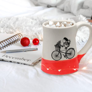 Handmade coffee mug with drawing of hedgehog delivering a Christmas tree on a bike. Red accent color.