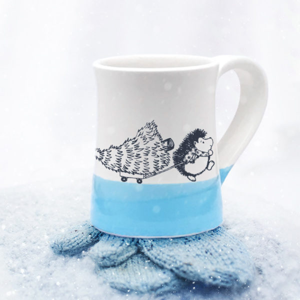 Handmade coffee mug with drawing of hedgehog pulling a Christmas tree on a little wagon. Blue accent color.