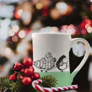 Handmade coffee mug with drawing of hedgehog pulling a Christmas tree on a little wagon. Green accent color.