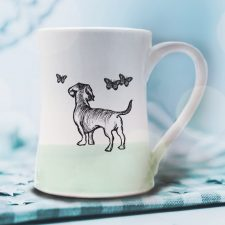 A handmade coffee mug with a drawing of a doggie hanging out with a bunch of butterflies. Green accent color.