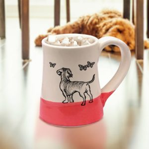 A handmade coffee mug with a drawing of a doggie hanging out with a bunch of butterflies. Red accent color.