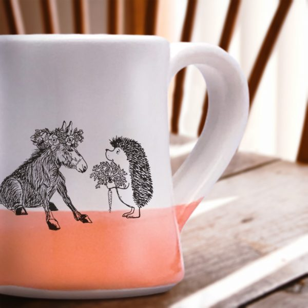 Just a sweet handmade mug with a roguish hedgehog offering a luscious carrot to a donkey princess. Coral accent color.