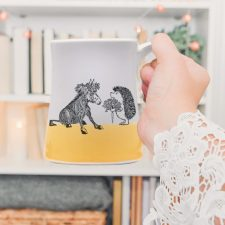 Just a sweet handmade mug with a roguish hedgehog offering a luscious carrot to a donkey princess. Gold accent color.