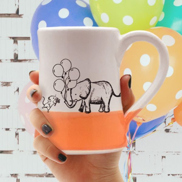 Handmade coffee mug with a drawing of a mouse and an elephant bringing each other gifts. Coral accent color.