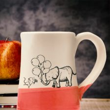 Handmade coffee mug with a drawing of a mouse and an elephant bringing each other gifts. Red accent color.