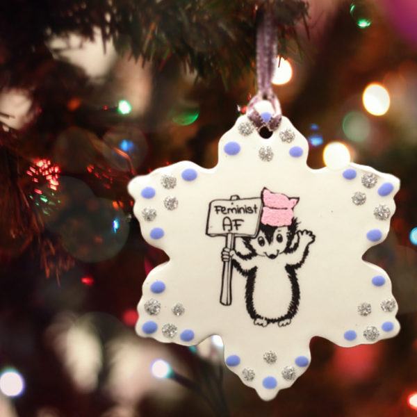 Handmade ceramic ornament with drawing of hedgehog holding a feminist as fuck protest sign. Joy to the girls.