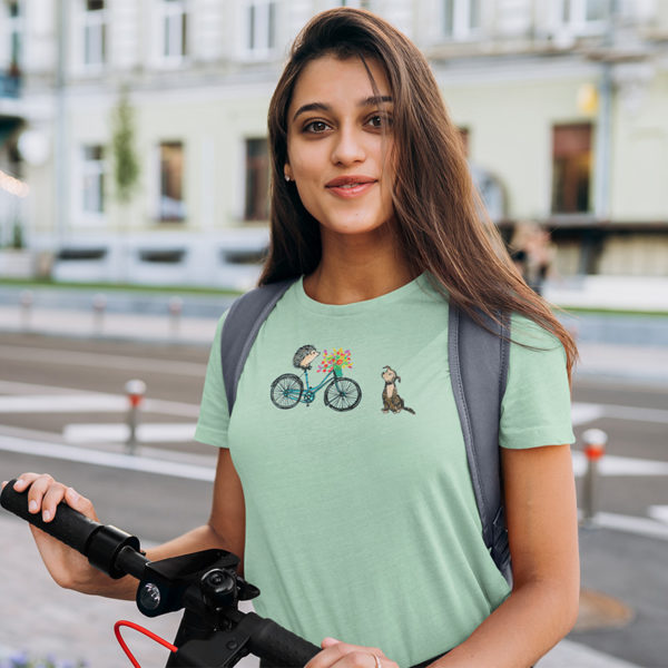 Woman wearing graphic T-shirt with original drawing of a hedgehog on a bike delivering flowers to a dog