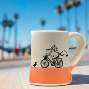 Handmade coffee mug with a drawing of a fox delivering beer on a bicycle. Now what could possibly go wrong? Coral accent color. Handmade coffee mug with a drawing of a fox delivering beer on a bicycle. Now what could possibly go wrong? Coral accent color.