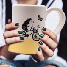 Handmade coffee mug with drawing of a hedgehog riding a bicycle while the duck navigates. Gold accent color.