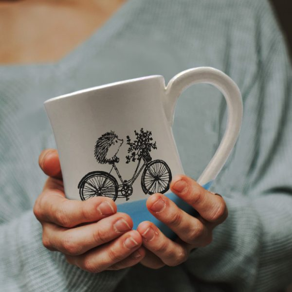A handmade coffee mug with a drawing of hedgehog on a bike delivering a basket of flowers. Blue accent color.