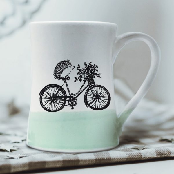 A handmade coffee mug with a drawing of hedgehog on a bike delivering a basket of flowers. Green accent color.