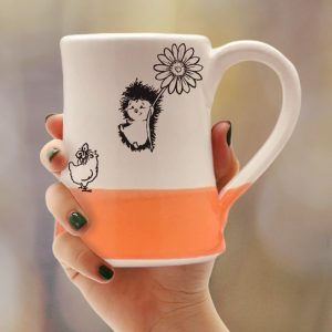 Coffee mug with drawing of a hedgehog flying on a flower to meet a surprised chicken. Coral accent color. Handmade in the USA by crafty hedgehogs.