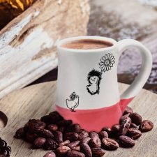 Coffee mug with drawing of a hedgehog flying on a flower to meet a surprised chicken. Red accent color. Handmade in the USA by crafty hedgehogs.