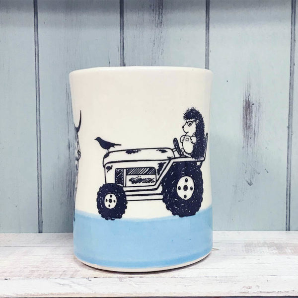 tumbler with drawing of a hedgehog in overalls riding a tractor with a cow in front