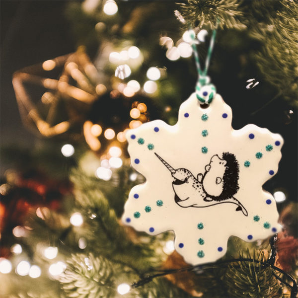 Handmade ceramic ornament with drawing of hedgehog riding a narwhal. Joyeux Narwhal to you!