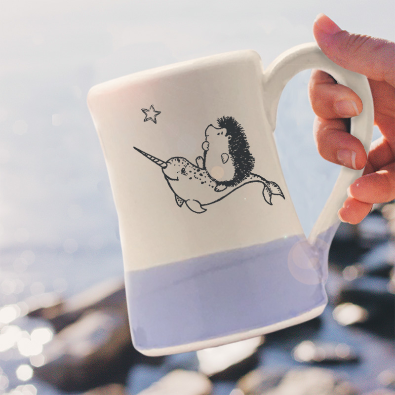 Handmade coffee mug with original illustration of a hedgehog riding on the back of a narwhal. Lavender accent color. Made by little crafty hedgehogs.