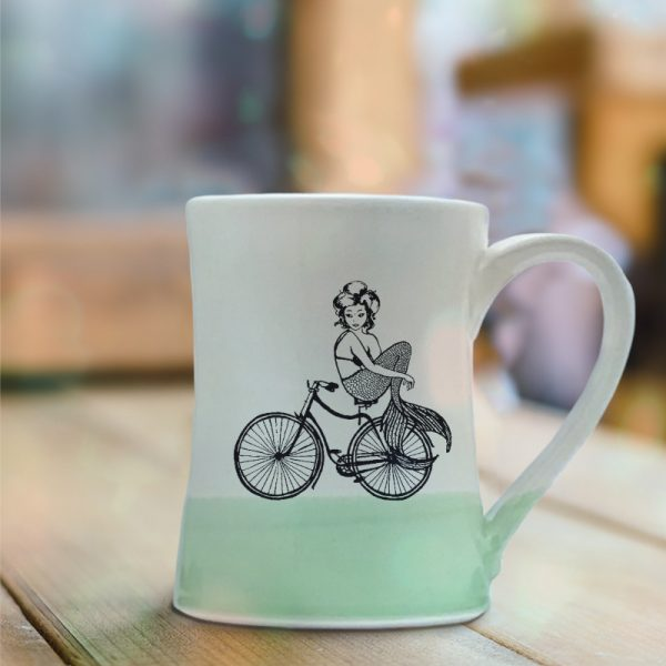 Handmade coffee mug with an undeterred mermaid riding a bicycle. She has a tail, nevertheless she is persisting. Green accent color.