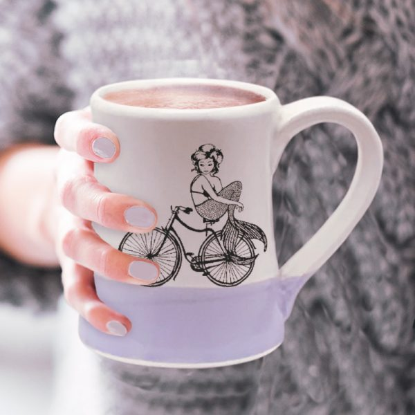 Handmade coffee mug with an undeterred mermaid riding a bicycle. She has a tail, nevertheless she is persisting. Lavender accent color.