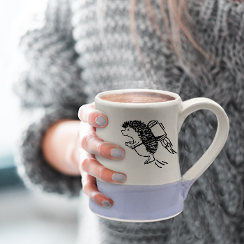 Woman wearing grey sweater holding mug