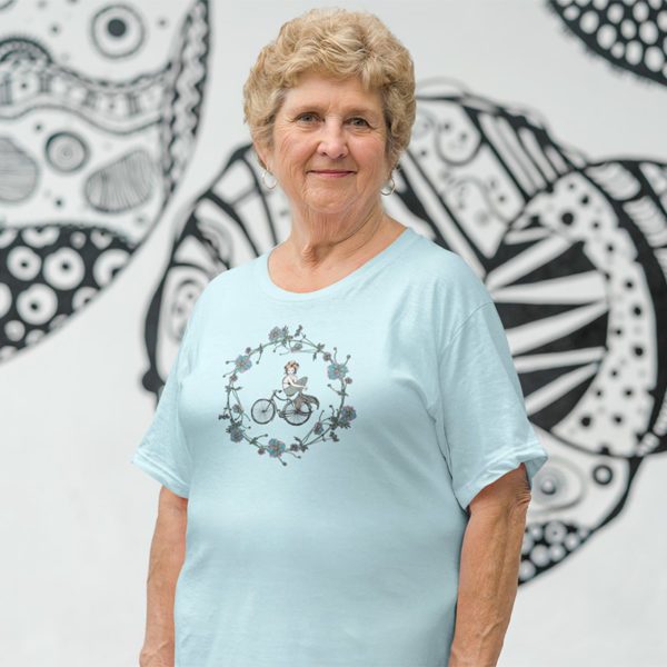 Woman wearing a graphic T-Shirt with original drawing of a mermaid on a bike