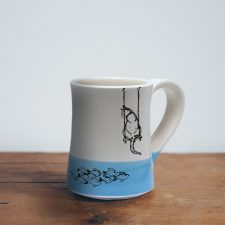 Coffee Mug created and illustrated by Darn Pottery hedgehogs depicts a tender moment between a feline and her breakfast. Blue accent color. For the cat lovers.