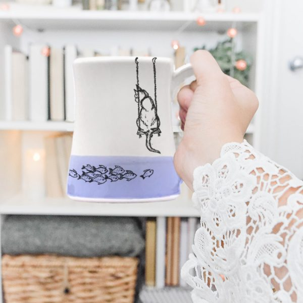 Coffee Mug created and illustrated by Darn Pottery hedgehogs depicts a tender moment between a feline and her breakfast. Lavender accent color. For the cat lovers.