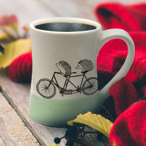 Handmade coffee mug with two happy hedgehogs on a tandem bike. Perhaps they are just married. Or besties out for a ride. Green accent color