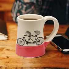 Handmade coffee mug with two happy hedgehogs on a tandem bike. Perhaps they are just married. Or besties out for a ride. Red accent color