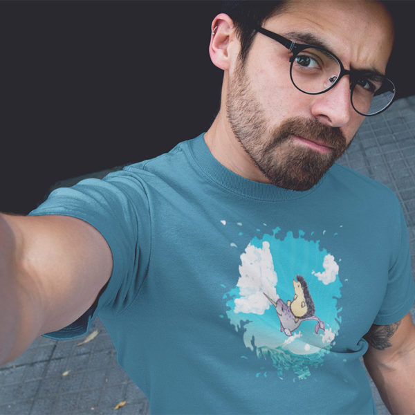 Man wearing a graphic T-shirt with original drawing of a hedgehog flying over the ocean on the back of a narwhal