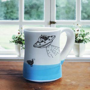 Handmade mug with a typical Darn Pottery illustration of a UFO and a dodo. Blue accent color.