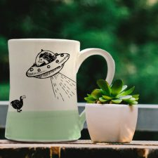Handmade mug with a typical Darn Pottery illustration of a UFO and a dodo. Green accent color.