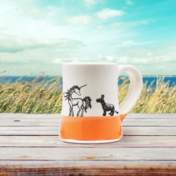 A handmade coffee mug with an illustration of a lovely unicorn and a pathetic little donkey who is in love. Coral accent color.