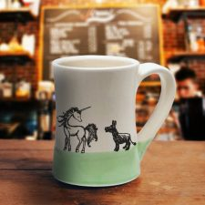A handmade coffee mug with an illustration of a lovely unicorn and a pathetic little donkey who is in love. Green accent color.
