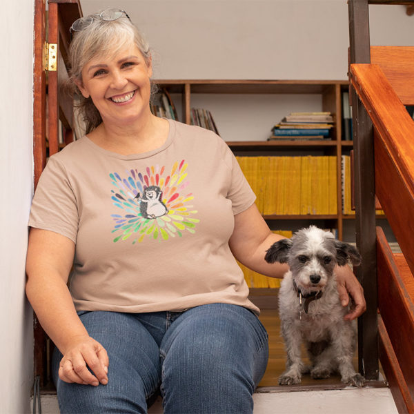 Woman wearing a graphic T-shirt with original drawing of a happy hedgehog talking to a bird on a splash of rainbow