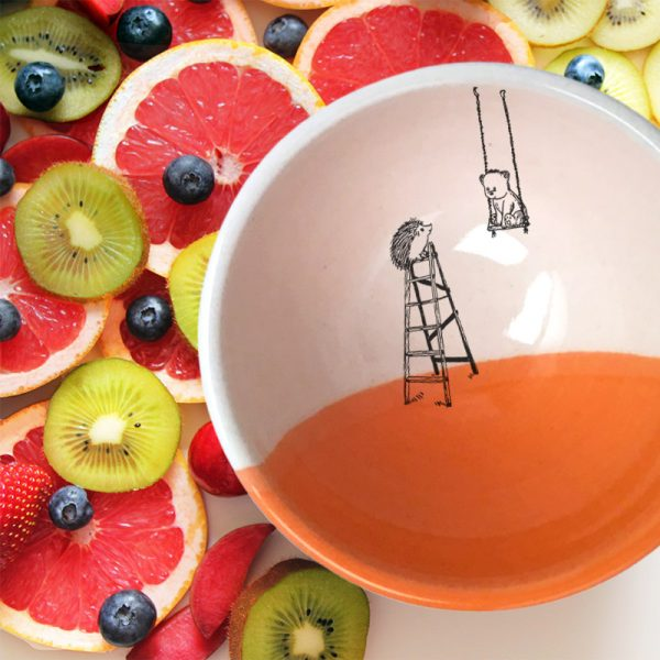 A handmade ceramic soup bowl with a drawing of a little bear in a swing and a hedgehog on a ladder. Coral accent color.