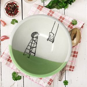 A handmade ceramic soup bowl with a drawing of a little bear in a swing and a hedgehog on a ladder. Green accent color.