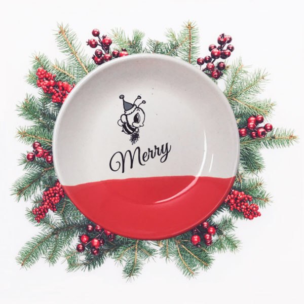 Handmade salad plate with drawing of a little bee in a Santa hat and the word Merry. Red accent color.