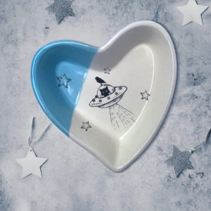 Handmade ceramic heart shaped dish with a drawing of a cat in a flying saucer or UFO. Blue accent color.