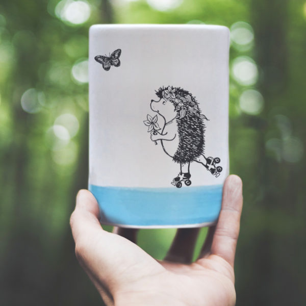 Handmade custom tumbler with drawing of a rollerskating hedgehog. Blue accent color
