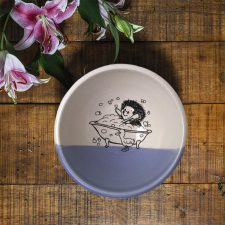 This handmade clay bowl features a funny drawing of a hedgehog taking a bubble bath in a claw-footed bathtub. Lavender accent color.