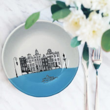 This ceramic plate is handmade by hedgehogs at Darn Pottery and has a drawing of Amsterdam canal houses and a little paper boat. Blue accent color