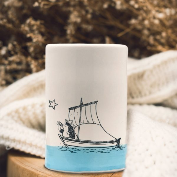 A handmade tumbler with a drawing of a hedgehog on a sailboat, probably plotting a daring exploit. Blue accent color.