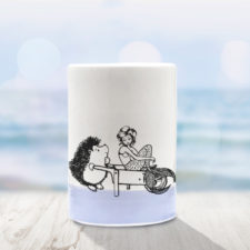 Handmade ceramic tumbler with drawing of a hedgehog and a mermaid in a wheelbarrow. Lavender accent color
