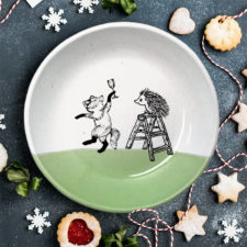 This plate is handmade by the hedgehogs of Darn Pottery and has a drawing of a fox celebrating with a champagne and a hedgehog climbing a ladder. Green accent color.